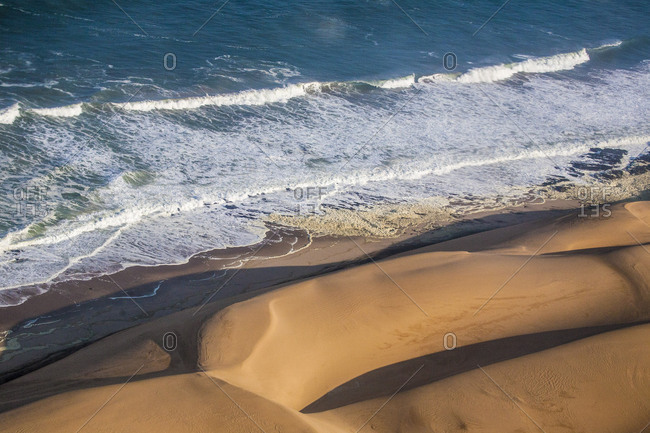 Aerial view of waves of the Atlantic Ocean crashing against the sandy dunes of the Namib desert Namibia Southern Africa