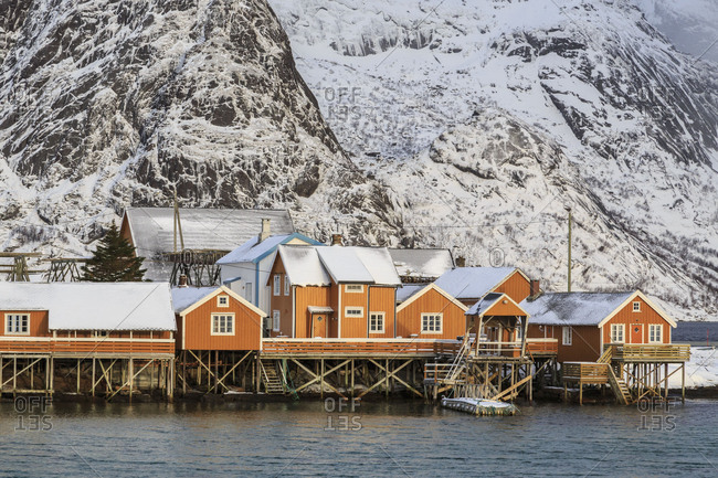 Typical wood houses of fishermen called rorbu framed by snowy peaks and the cold sea Hamnoy Reine Lofoten Islands Norway Europe