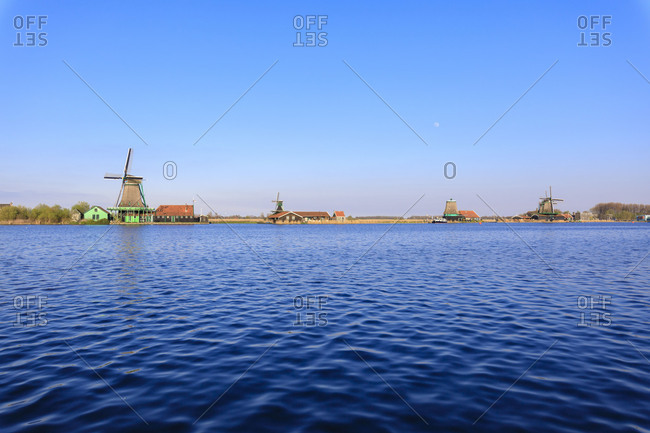 Typical windmills reflected in the blue water of river Zaan in spring Zaanse Schans North Holland The Netherlands Europe