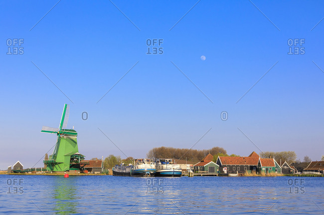 June 27, 2017: Typical windmill and boats in the fishing village of Zaanse Schans framed by river Zaan North Holland The Netherlands Europe