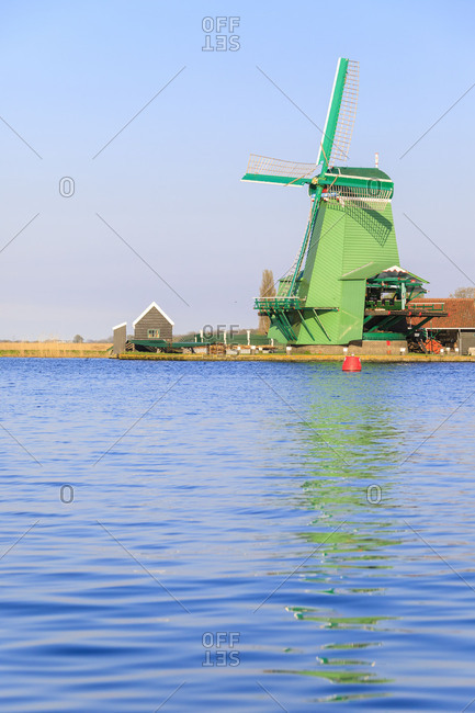 Typical windmill reflected in the blue water of river Zaan in spring Zaanse Schans North Holland The Netherlands Europe