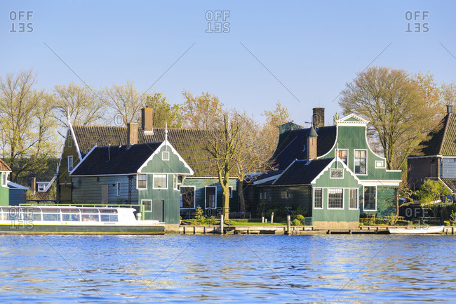 Typical wooden houses of the fishing village of Zaanse Schans framed by river Zaan North Holland The Netherlands Europe
