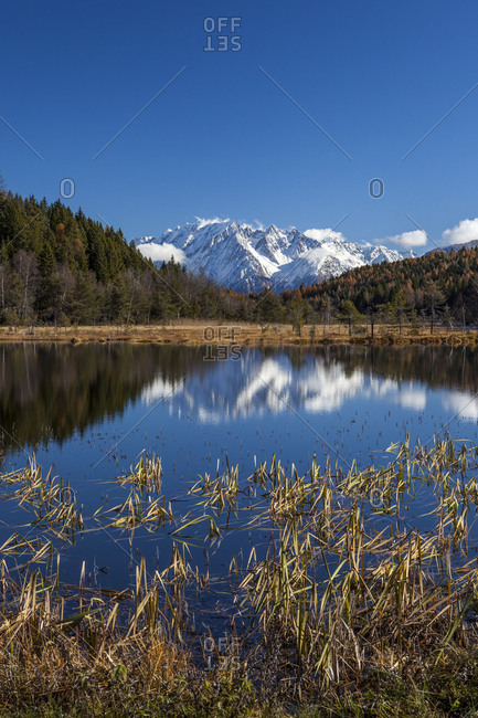 Snowy peaks reflected in the blue water of the Natural Reserve of Pian di Gembro Aprica Sondrio Valtellina Lombardy Italy Europe