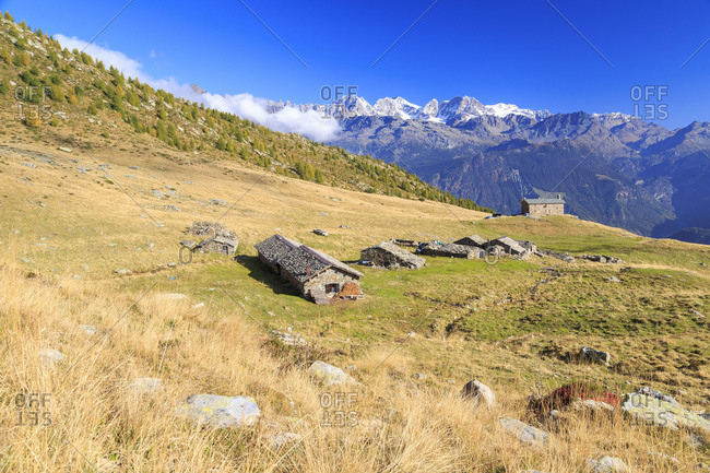 Alpine huts framed by snowy peaks of Bernina Group Arcoglio Alp Val Torreggio Malenco Valley Valtellina Lombardy Italy Europe
