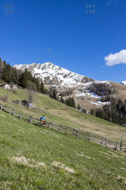 Mountain bike on green meadows framed by snowy peaks in spring Albaredo Valley Orobie Alps Valtellina Lombardy Italy Europe