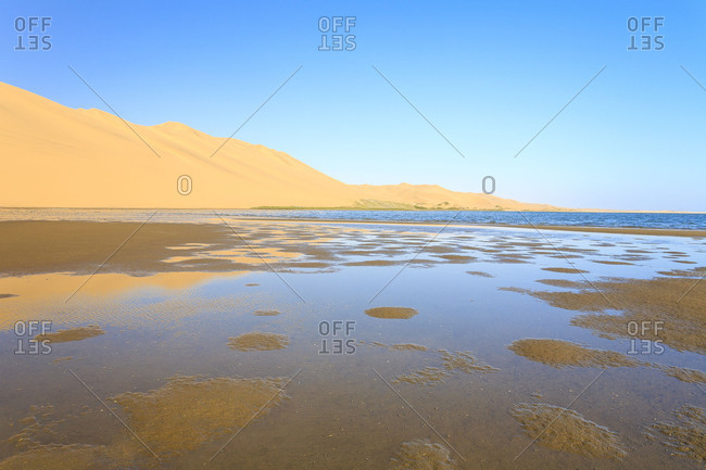 Sand dunes reflected in the lagoon beside the Atlantic Ocean Walvis Bay Namib Desert Erongo Region Namibia Southern Africa