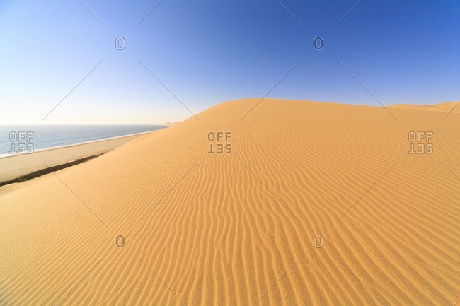 Sand dunes modeled by wind meet the Atlantic Ocean Walvis Bay Namib Desert Erongo Region Namibia Southern Africa