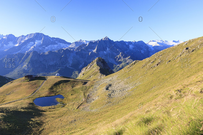 Green meadows and alpine lake framed by the high peaks in the Adamello Ski Area pass Tonale Valcamonica Lombardy Italy Europe