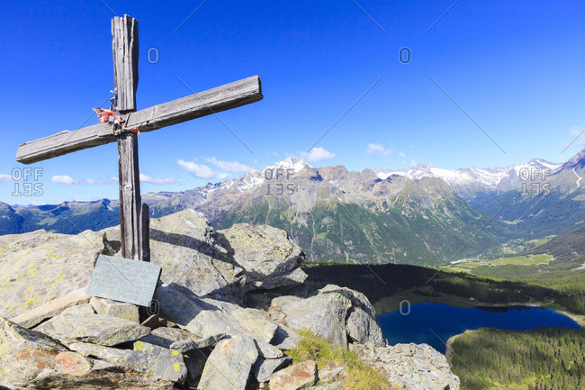 Wood cross above Lake Palu framed by Mount Disgrazia seen from Monte Roggione Malenco Valley Valtellina Lombardy Italy Europe