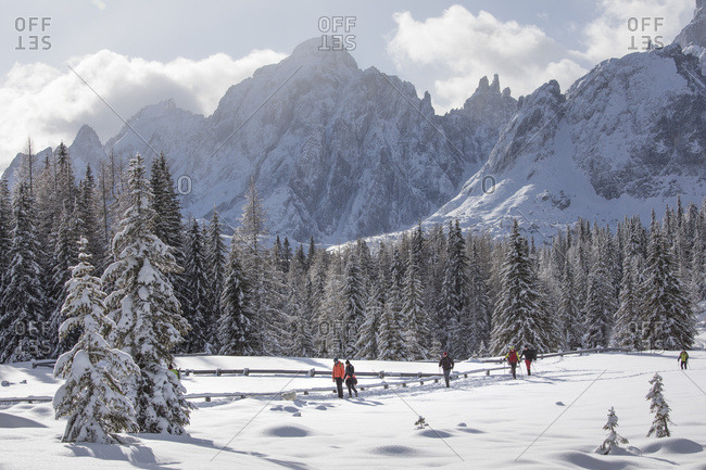 December 17, 2017: Hikers in the path leading to the Nemes, on background the peaks of the Comelico Superiore, Sesto, Pusteria valley, Trentino Alto Adige, Italy, Europe