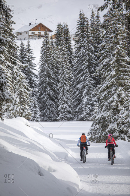 December 17, 2017: Two bikers along the path leading to the Nemes refuge in the backgroud, Sesto, Pusteria valley, Trentino Alto Adige, Italy, Europe
