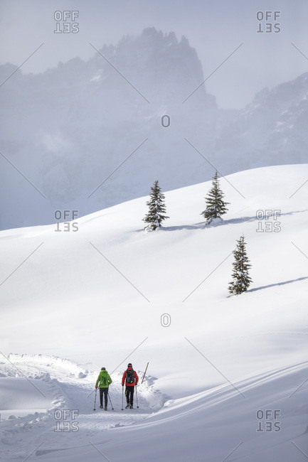 December 17, 2017: Hikers in the Nemes alp, in the background the Tre Scarperi mount, Sesto, dolomites, Pusteria valley, Trentino Alto Adige, Italy, Europe