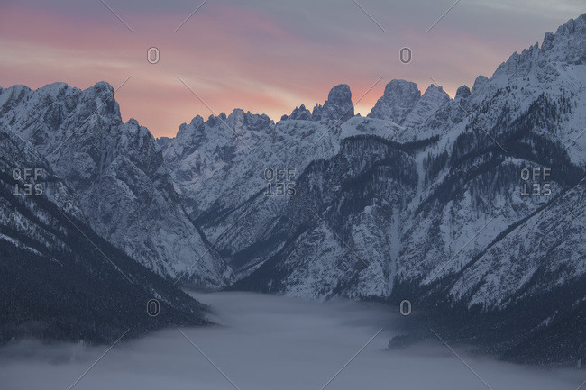 The peaks above the village of Dobbiaco covered by low clouds, in the background Cristallo and Piz Popena mount, Pusteria valley, dolomites, Trentino Alto Adige, Italy, Europe