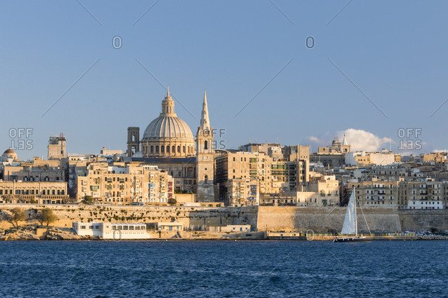 October 27, 2017: Panoramic view of Saint Paul's Cathedral and the ancient walls of Valletta with sail boat at the sunset, Malta, Europe