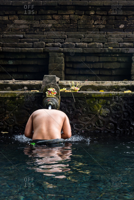 man bathing in the waters of the Tirta Empul Water Temple, Ubud, Bali