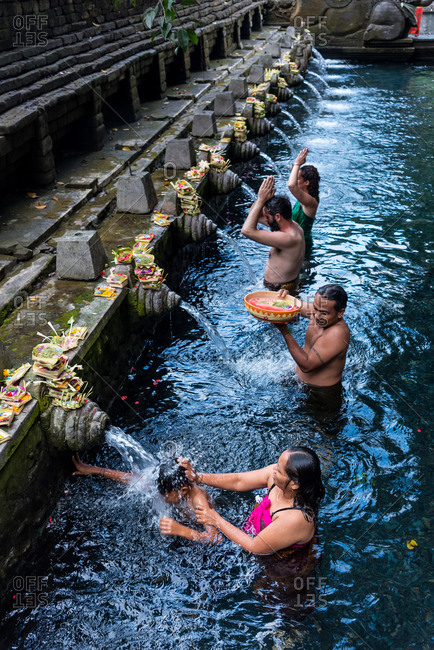 July 5, 2018: Bali, Indonesia July, 5, 2018: People bathing in the waters of the Tirta Empul Water Temple, Ubud, Bali