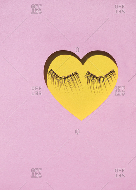 False eyelashes creating a face on a yellow hard on a pink construction paper background
