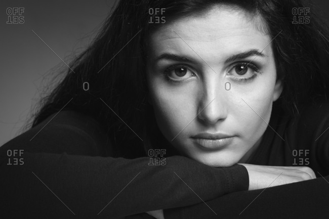 Young attractive woman leaning her chin on her arms and looking at camera
