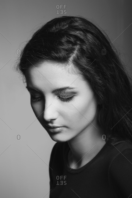 Beautiful young woman looking down and thinking