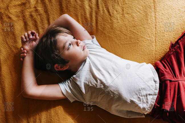 Portrait of a young boy playing on a bed