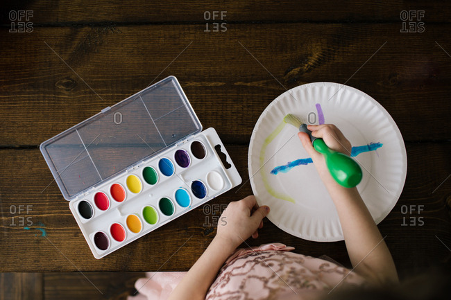 Child painting with watercolors on a paper plate