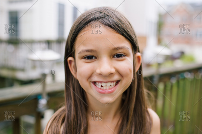 Portrait of a smiling girl with brown hair and brown eyes