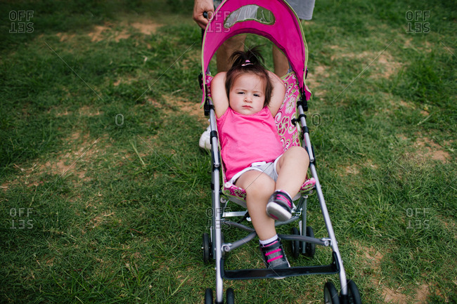 Baby relaxing in pink stroller with hands behind head