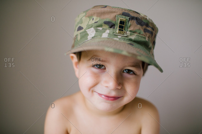 Portrait of a smiling boy wearing a camouflage hat