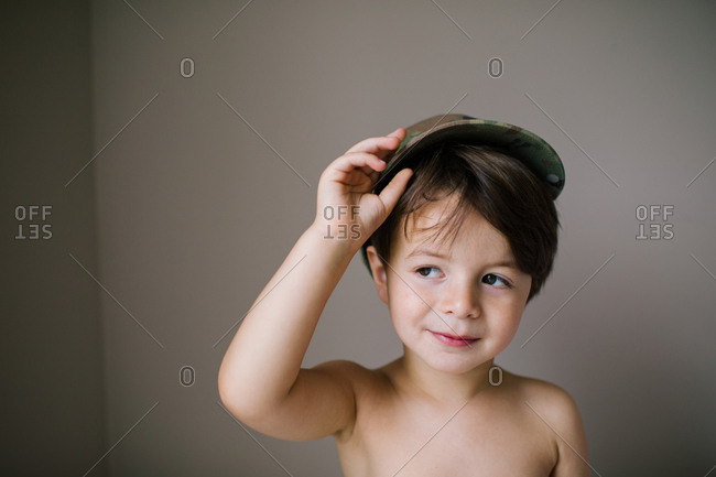 Portrait of a boy tipping hat and looking to side