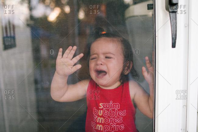 Crying baby pressing hands against screen door