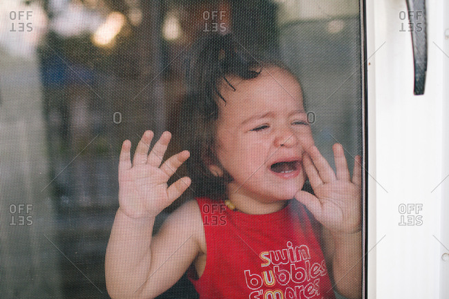 Crying baby pressing against screen door