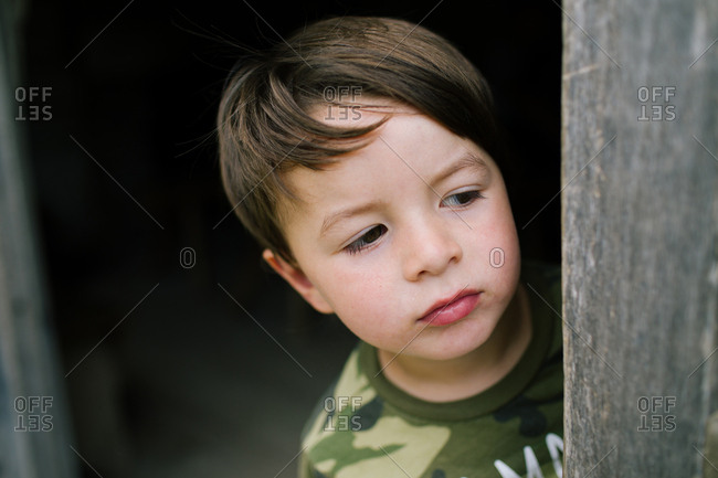 Portrait of a boy looking around corner