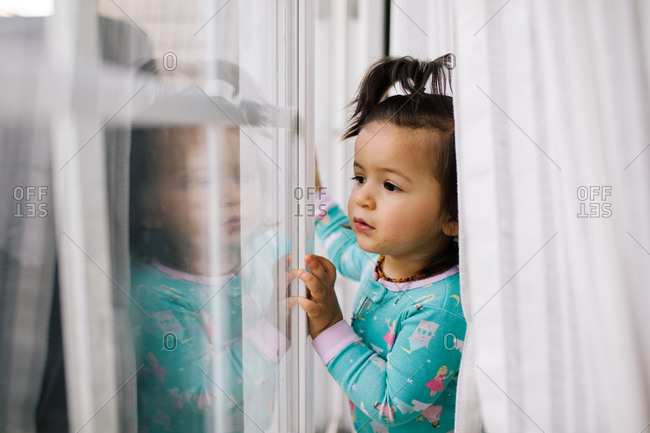 Toddler girl behind drapes looking out window