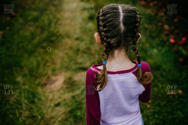 Back view of girl with braided hair standing outside