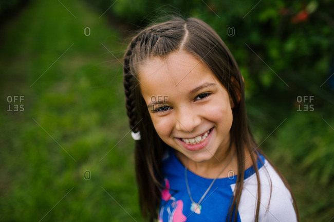 Portrait of a smiling girl with long brown hair standing outside