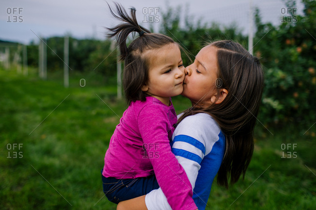 Girl holding and kissing her younger sister