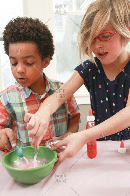 Girl and boy mixing ingredient in bowl to make slime at table in house
