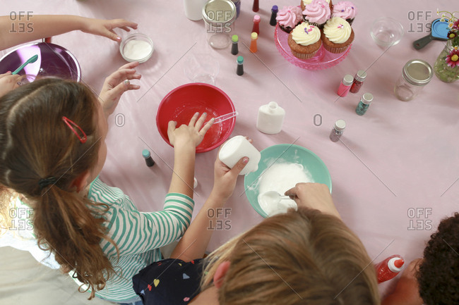 Boy making slime with friends at table in house