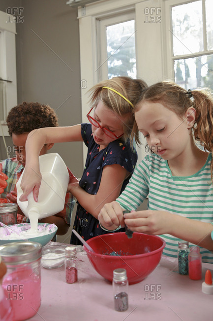Girl pouring glue in mixing bowl while making slime with friends at home
