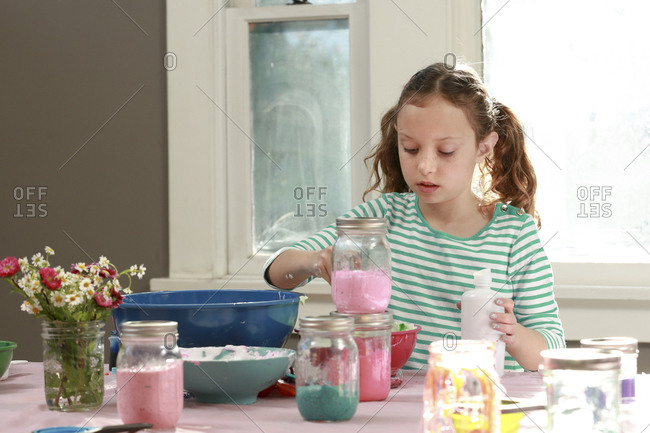 Young girl mixing ingredients in bowl to make slime at home