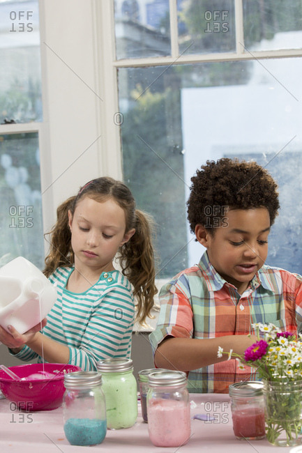 Multiethnic boy and girl preparing slime at table in house