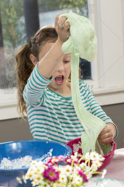 Shocked girl stretching slime from mixing bowl at home
