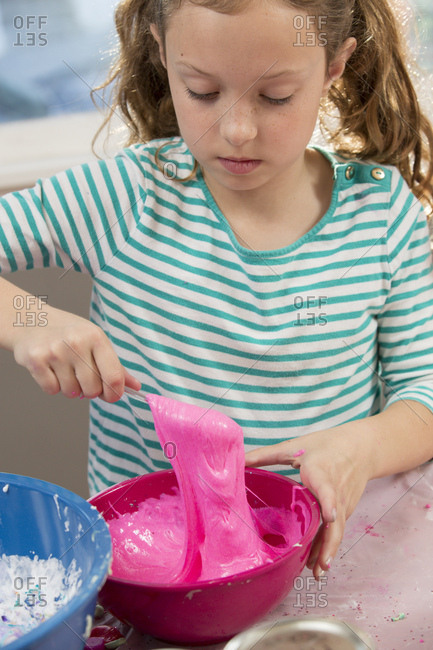 Cute girl mixing pink glitter slime with spoon in bowl at home