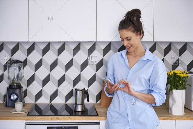 Young woman preparing coffee in the morning- using smartphone