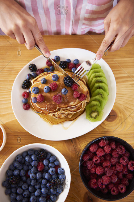 Woman eating pancakes with berries for breakfast