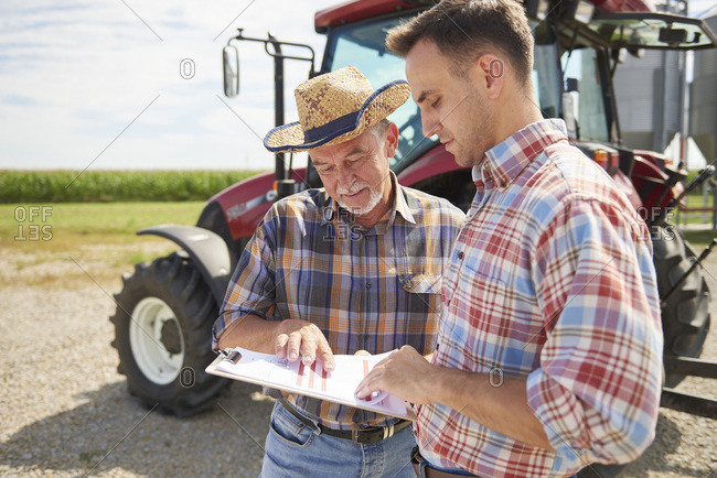 Two farmers looking at data from clipboard on the farm
