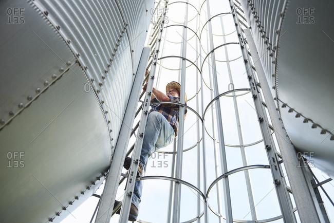 Farmer climbing up ladder at tank