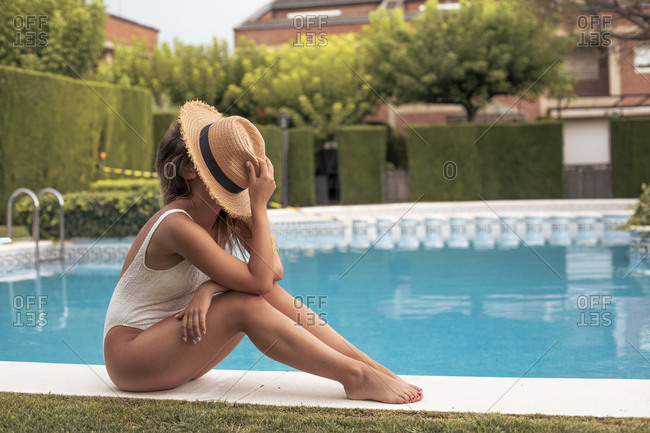 Portrait of an unrecognizable girl sitting in the pool with a straw hat on her face
