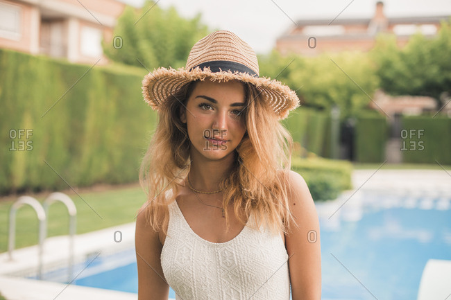 Portrait of young woman with straw hat and swimsuit- pool in the background