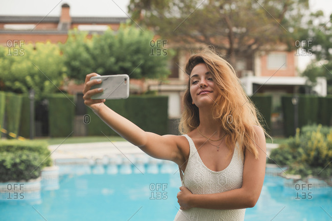 Portrait of young woman in a swimsuit making a selfie with the pool in the background